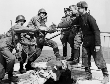 02 May 1945, Torgau, Germany --- Original caption: 5/2/1945-Torgau, Germany- This historic incident, which occurred on the wrecked bridge over the Elbe River at Torgau, shows the first meeting of American (L), and Russian soldiers as they reach out to grasp each other's hands. BPA2 # 5663 --- Image by © Bettmann/CORBIS