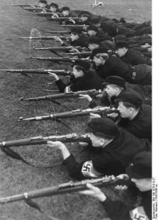 Vormilitärische Ausbildung im Bann-Lager der Hitler-Jugend. Während in den Wehrertüchtigungslagern der HJ in der Hauptsache auf die körperliche Ausbildung der Jungen wert gelegt wird, sie also vor allen Dingen in den verschiedensten Sportarten geschult werden, sind die Bannlager der Hitler-Jugend ausschließlich auf die Waffentechnische Ausbildung eingestellt. UBz: Bei Übungen am Gewehr. Jeder Junge muß seine Waffe genau kennen, bevor er sie auf das Ziel anlegen darf. Foto: Hamann