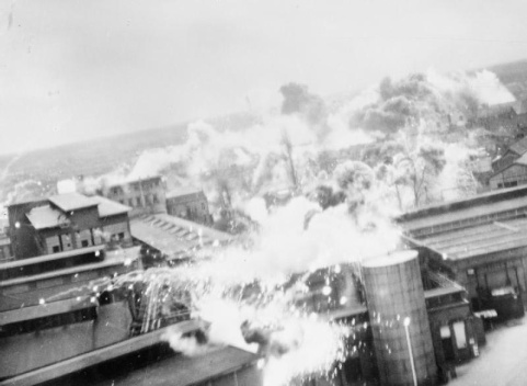 Operation OYSTER, the daylight attack on the Philips radio and valve works at Emmasingel, Eindhoven, Holland, by No. 2 Group. Low-level oblique photograph showing incendiary bombs dropped by Lockheed Venturas bursting on the roof of the Emmasingel lamp and valve factory. C 3268 Part of AIR MINISTRY SECOND WORLD WAR OFFICIAL COLLECTION No. 21 Squadron RAF