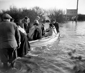 Wrapped in blankets, children and adults are ferried by boat through the flood waters at Jaywick, near Clacton, essex, after the disastrous storms that hit the south east.