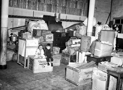 Mar. 24, 1942: Two small children of Japanese evacuees from San Pedro sit atop luggage piled in kindergarten roon at Hongwanjo Buddhist Temple in Little Toyko. This photo was published in the Mar. 25, 1942, Los Angeles Times.