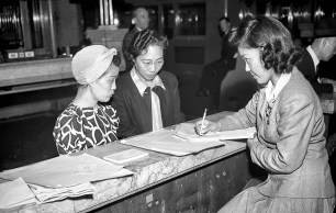 Mar. 30, 1942: Two Japanese women get information from Japanese clerk regarding plans for their removal. Photo was published Mar. 31, 1942 with story announing the removal of all Japanese from the Los Angeles Harbor area.