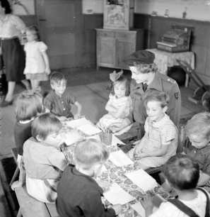 Miss S J Reekie, a British trained nurse and child welfare specialist works with the very young children in the kindergarten set up at Belsen after the liberation of the camp. All the children in the photograph were orphans BU 7801 Part of WAR OFFICE SECOND WORLD WAR OFFICIAL COLLECTION No 5 Army Film & Photographic Unit Hewitt (Sgt)