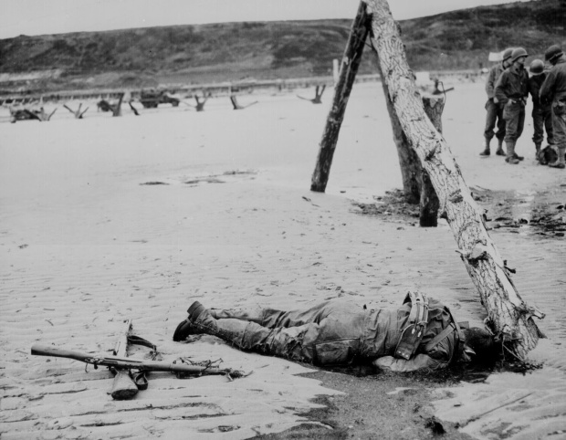 Crossed rifles in the sand placed as a tribute to this fallen soldier, 1944