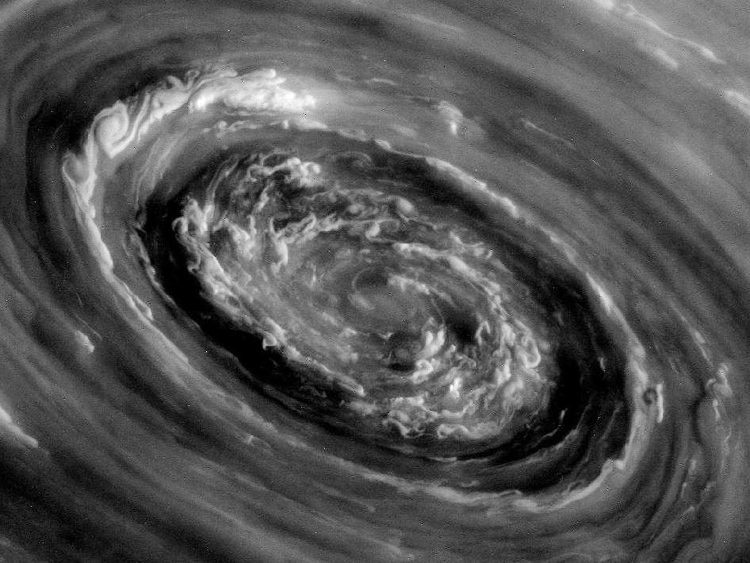 Storm clouds and a swirling vortex at the center of Saturn's north polar hexagon is seen in an image from NASA's Cassini mission