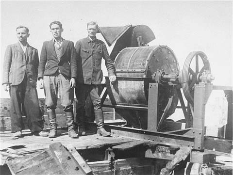 Members_of_a_Sonderkommando_1005_unit_pose_next_to_a_bone_crushing_machine_in_the_Janowska_concentration_camp