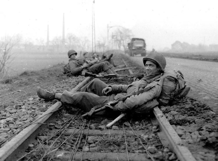Battle-of-the-Bulge-Tour-During-the-Battle-of-the-Bulge-GIs-of-the-Timberwolf-Division-resting-on-the-rails-after-combat-in-Düren-21-December-1944-Virtuoso-Battle-Tours