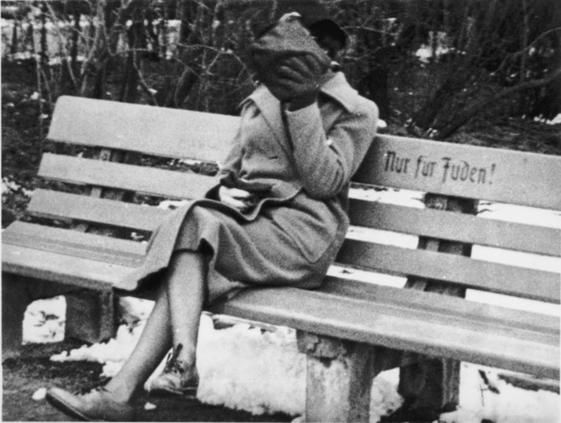 A Jewish woman who is concealing her face sits on a park bench marked Only for Jews, Austria, 1938